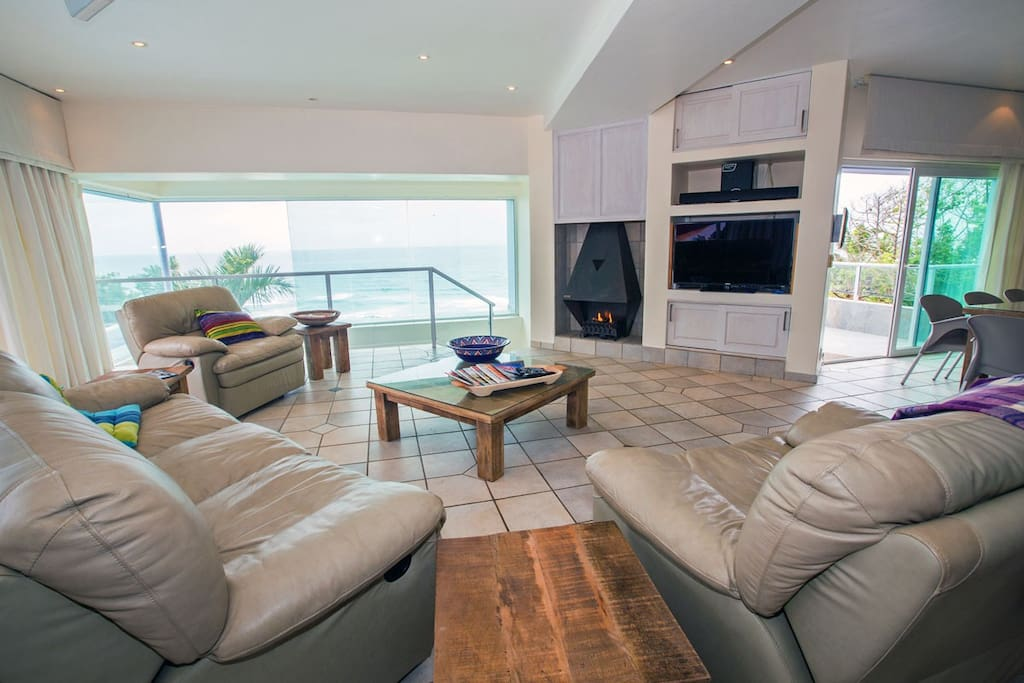 The living area has full ocean view, reclining sofas, a fireplace and satellite television.