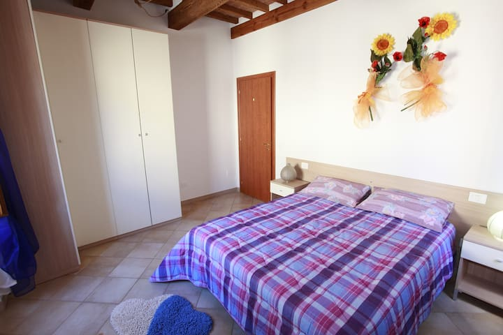 ampia camera matrimoniale con doppia finestra, armadio, cassettiera e TV