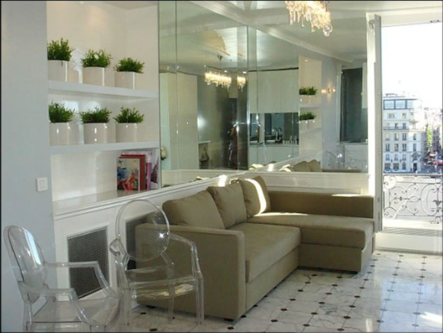 The fold-out sofa/bed, Starck design chairs and original 17th century marble floor