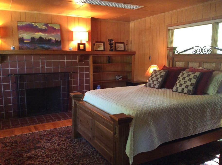 Main bedroom has a queen size bed, fire place, recliner, desk and chair.