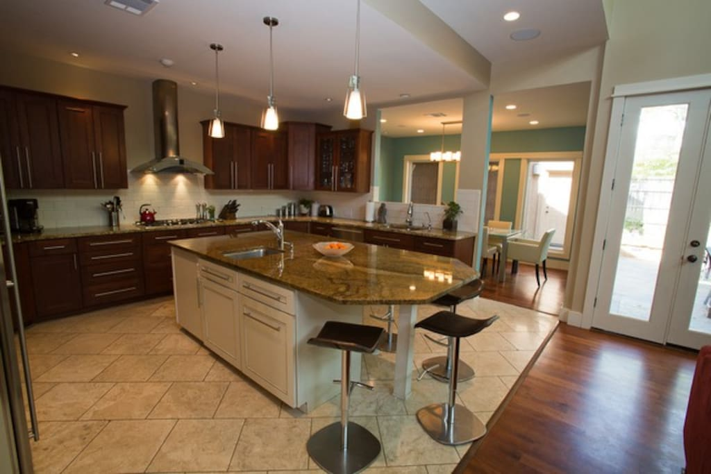 Large kitchen featuring island that seats 4, 2 sinks, stainless steel appliances, and granite