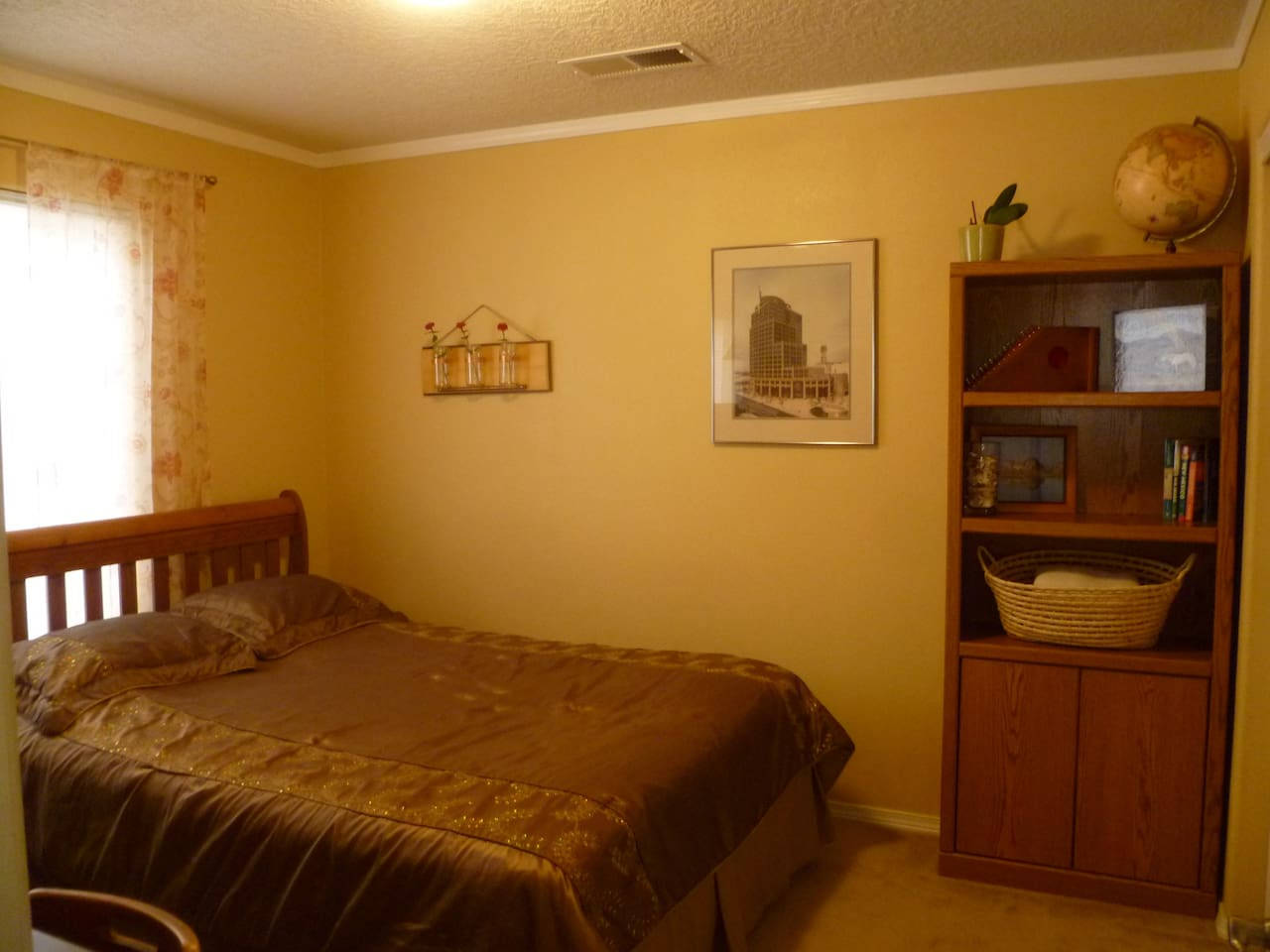 Comfortable private bedroom with Queen-sized bed, desk and ceiling fan.