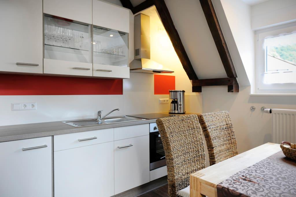 Voll ausgestattete Küche inkl. Herd/Ofen, Kühlschrank und Kaffeemaschine.