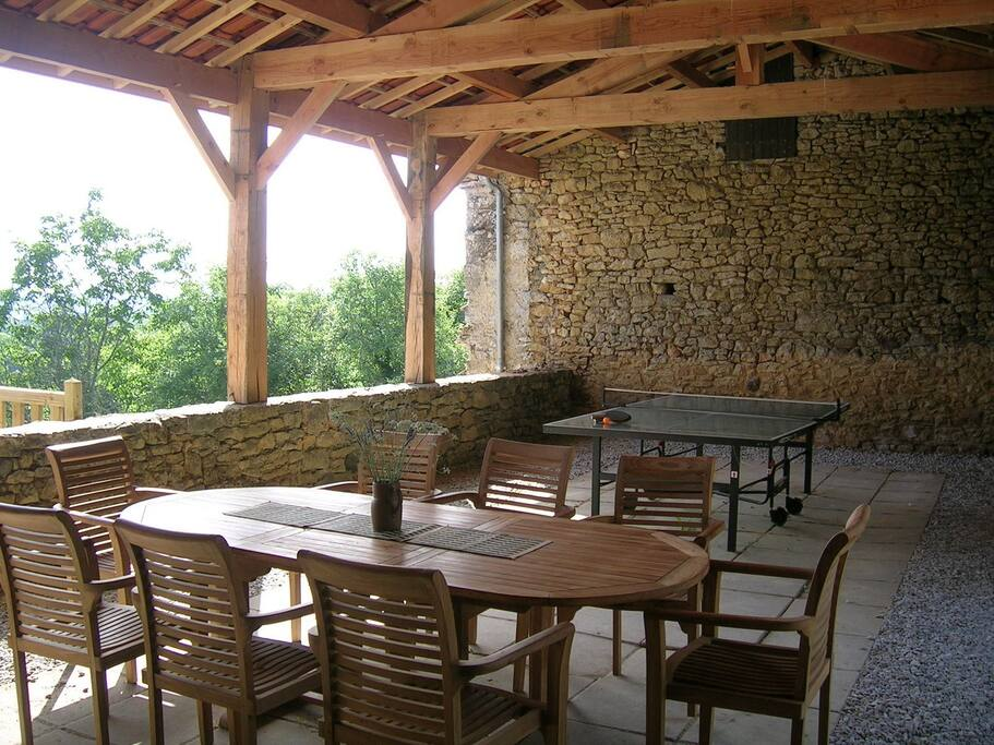 L'immense terrasse couverte avec un barbecue