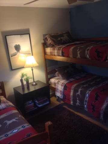 The guest bedroom features bunk beds, built in closets and drawers