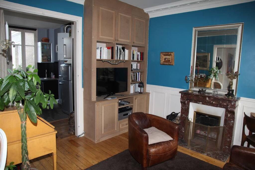 Le salon coté cheminée, avec la télévision et la cuisine ouverte.