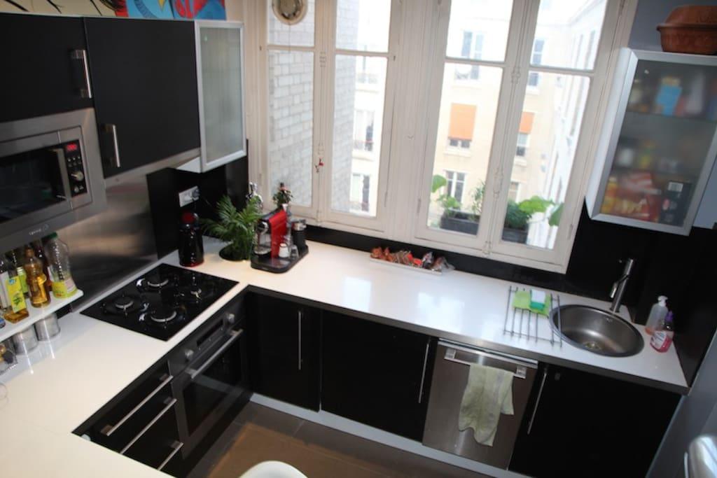 La cuisine ouverte entièrement équipée donnant sur la cour intérieure.