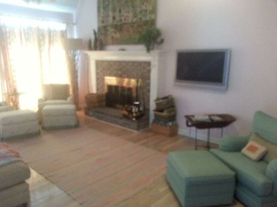 Great room with working fire place, big screen tv, wood floors, L shape