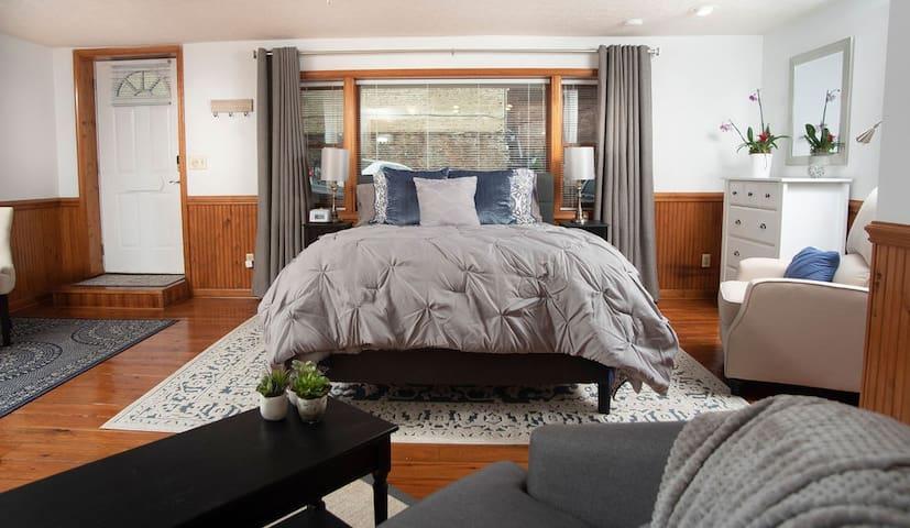 Bedroom area includes queen bed, dresser, & recliner