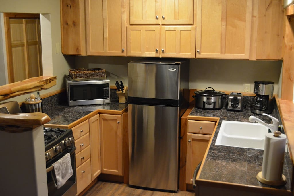 Gas range and all new appliances. Kitchen stocked with solid cookware, knives, and accessories.