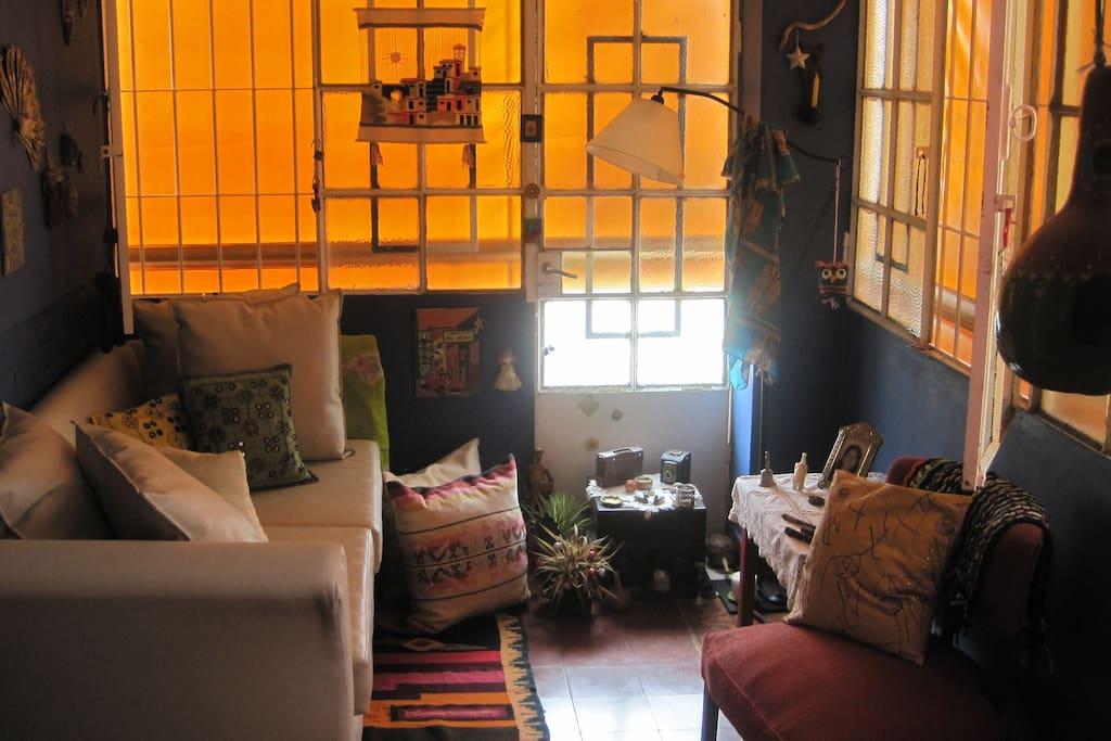 Living con comodo sillón y amplias mamparas para dejar entrar la luz.