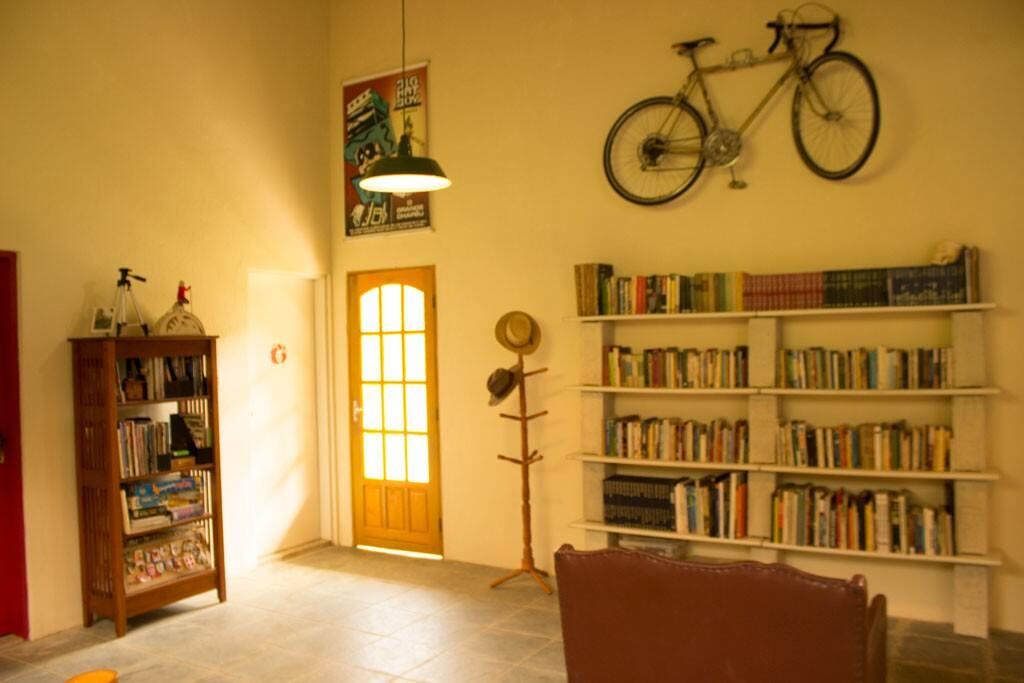 Amplo salão social, com biblioteca, espaço para refeições e TV