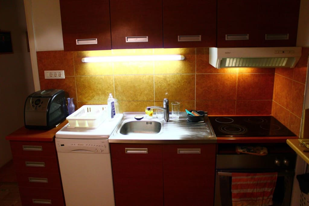 The kitchen - breadmaker, dishwasher, sink, oven and ceramic heating plate.