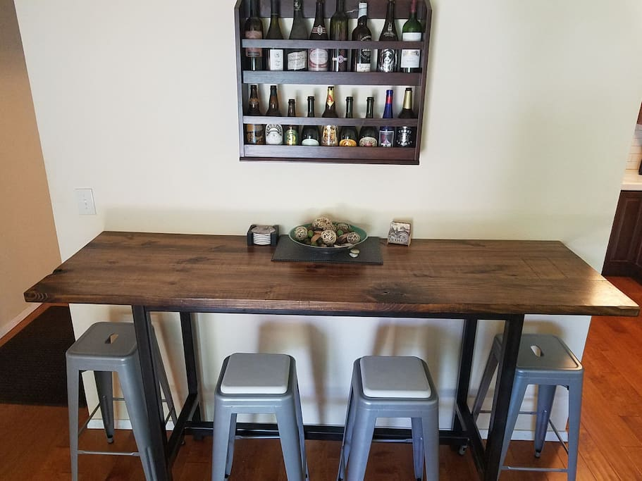 Standing/Bar height work/recreation table in the living room. Perfect for dining, working or playing cards. Hall of fame beer and wine collection on the wall.
