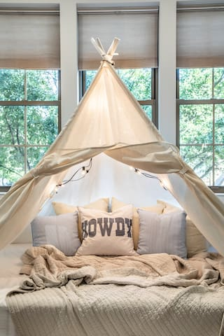 Lounge or sleep in the tipi with a queen mattress, canvas doors, and fun lighting.