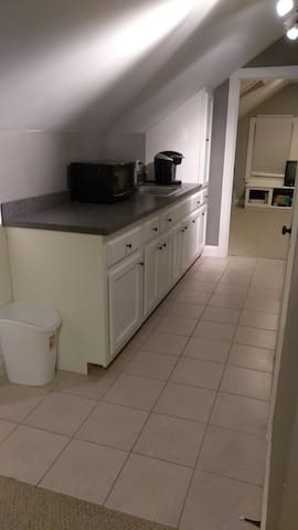 Kitchenette with microwave, sink, and fridge/freezer.