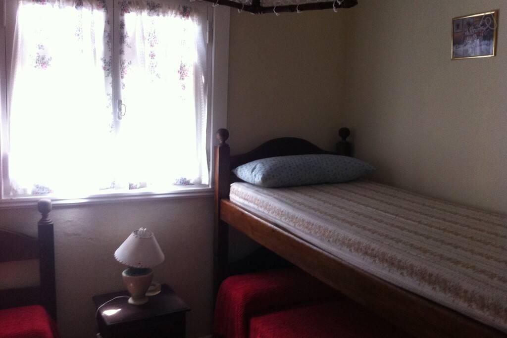 Habitación con una cama simple y una litera