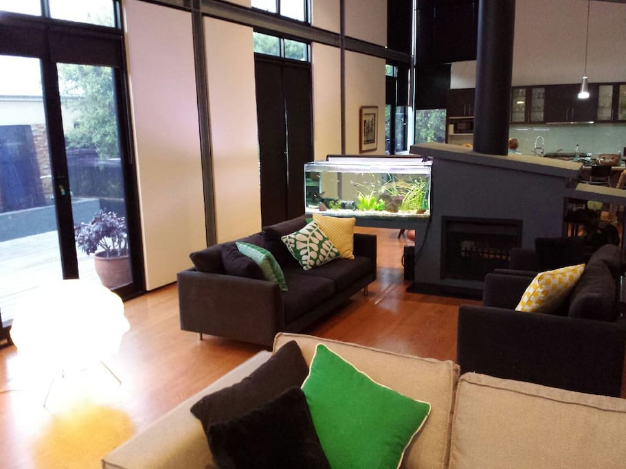 Open plan living area with large fish tank leading out to open outdoor entertainment area and hot tub.