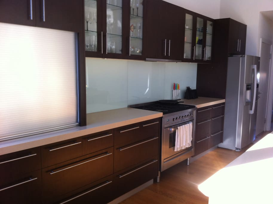 Modern open plan kitchen fully equipped with Ilve stove top and granite benches plus coffee machine.