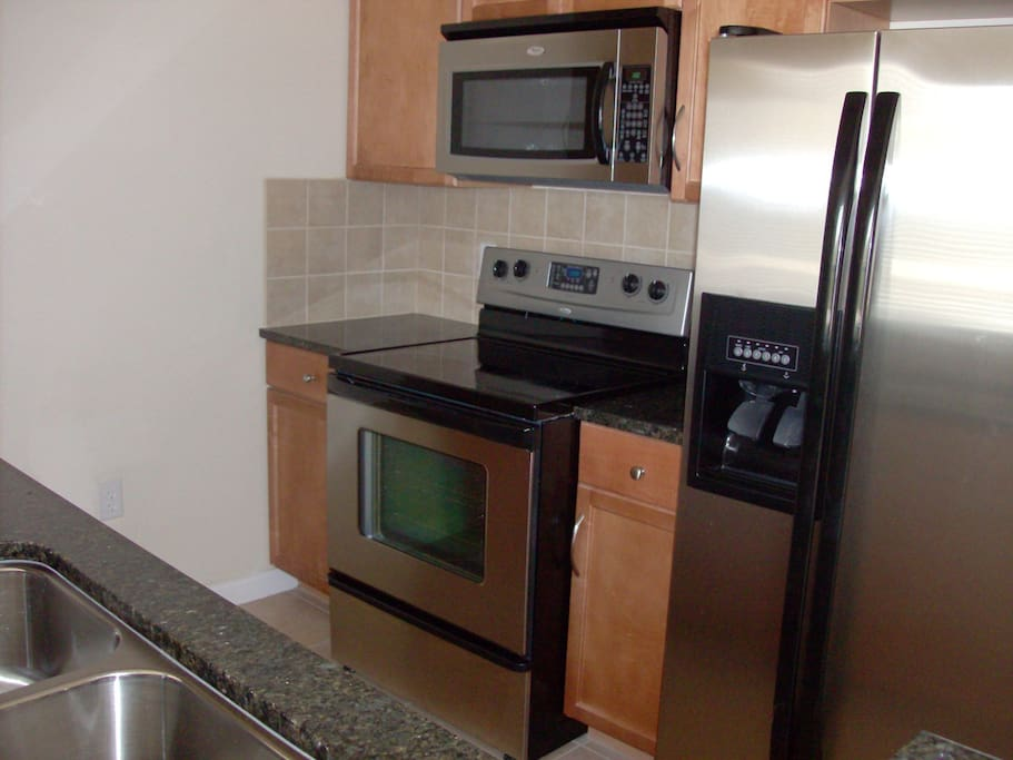 Fully equipped kitchen with granite countertops and stainless steel appliances.
