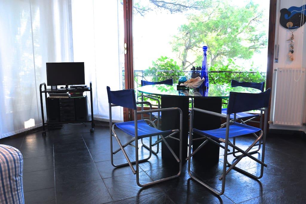 Dal terrazzo direttamente in soggiorno con ampie vetrate e angolo cucina
