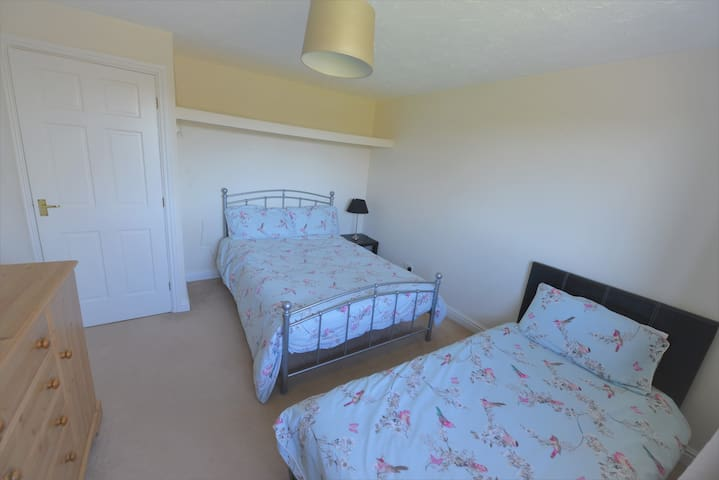 Front bedroom 4 with one double and one single bed; wardrobe / hanging and chest of drawers. Views to countryside.