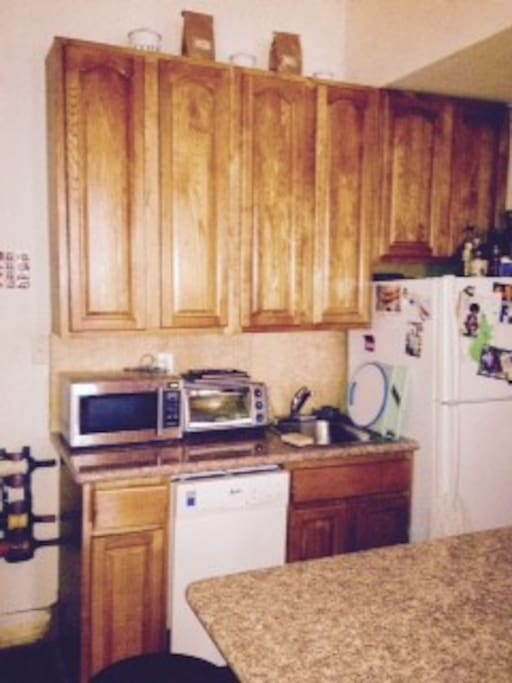 Full kitchen with stove, oven and dishwasher, microwave, toaster oven and full set of cooking implements.