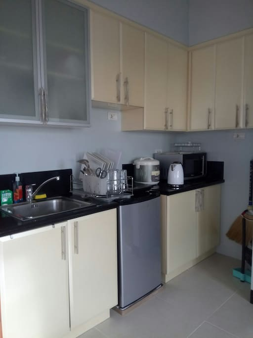 KITCHEN: Cupboards with toaster, Sink with sponge and soap, Fridge, Kettle, Dish rack; complete with Plates, Spoon and fork, knife and chopping board, Microwave and bin 1 hub Induction cooker, Rice cooker, hotpot, wok and a cooking utensil