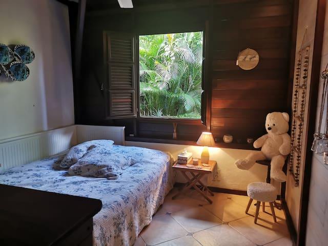 Chambre avec brasseur d'air et vue sur le petit potager