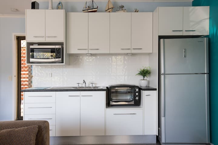 Fully self contained kitchenette with full size fridge - micro wave, fry pan, toaster, sandwich maker, induction hot plate and pots, small oven and all utensils needed.