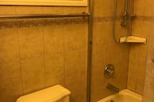 Private bathroom with shower and bathtub