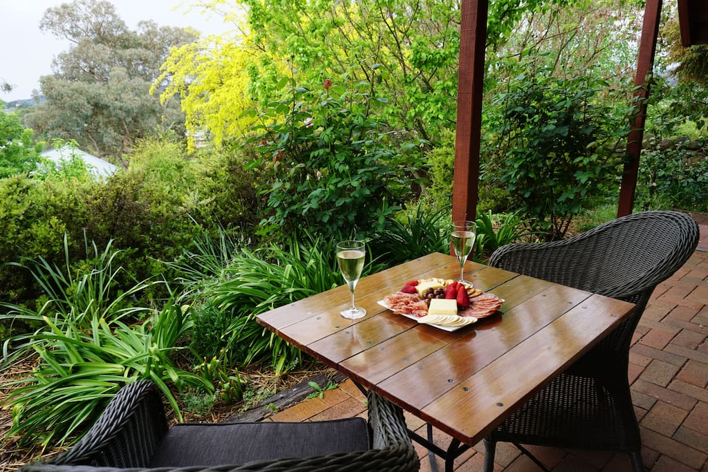 Outdoor sitting area surrounded by gardens. Under cover so may be enjoyed rain, hail or shine