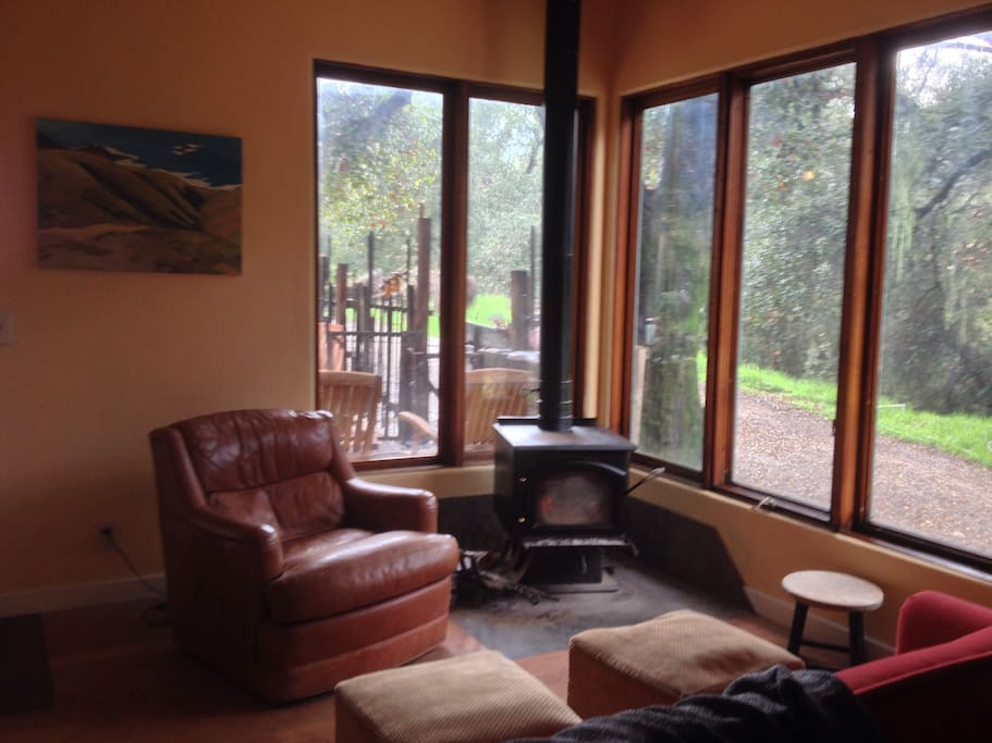 A wood stove heats the Barn on cold days. Large windows look out to covered patio, fenced yard and oaks.