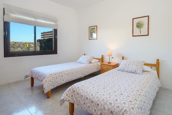 dormitorio de dos camas y con vistas al jardin ,donde tambien podran disfrutar de un bonito atardecer con vistas a las montañas.