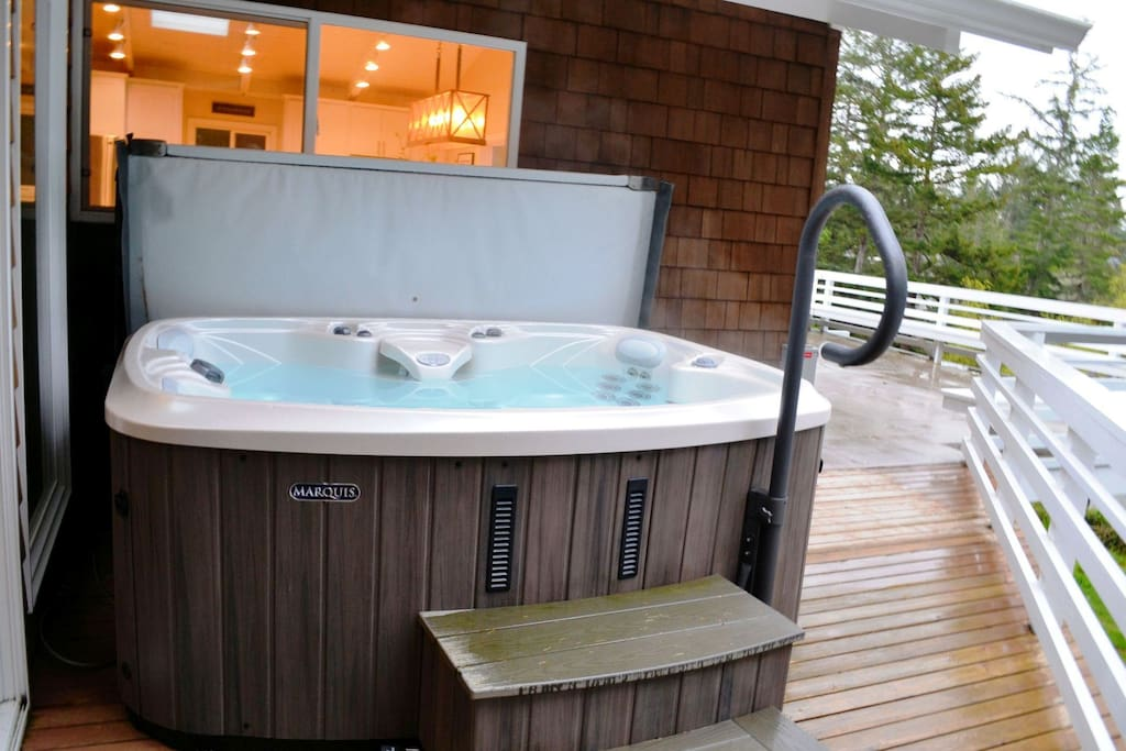 Large upper deck with a hot tub, charcoal BBQ, patio table with chairs and stairs to lower patio
