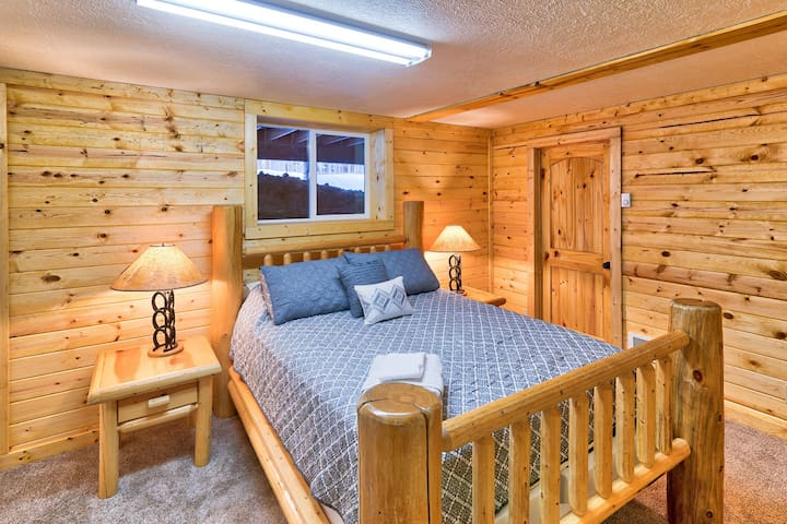 Bedroom 4: Beautiful wood adorn the walls bringing the outdoor in in this beautiful cabin home.