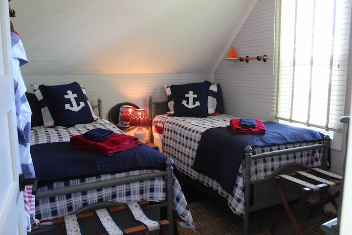 Bedroom 1 has 2 twin beds, a large dresser and 2 suitcase stands and a view of the lake.