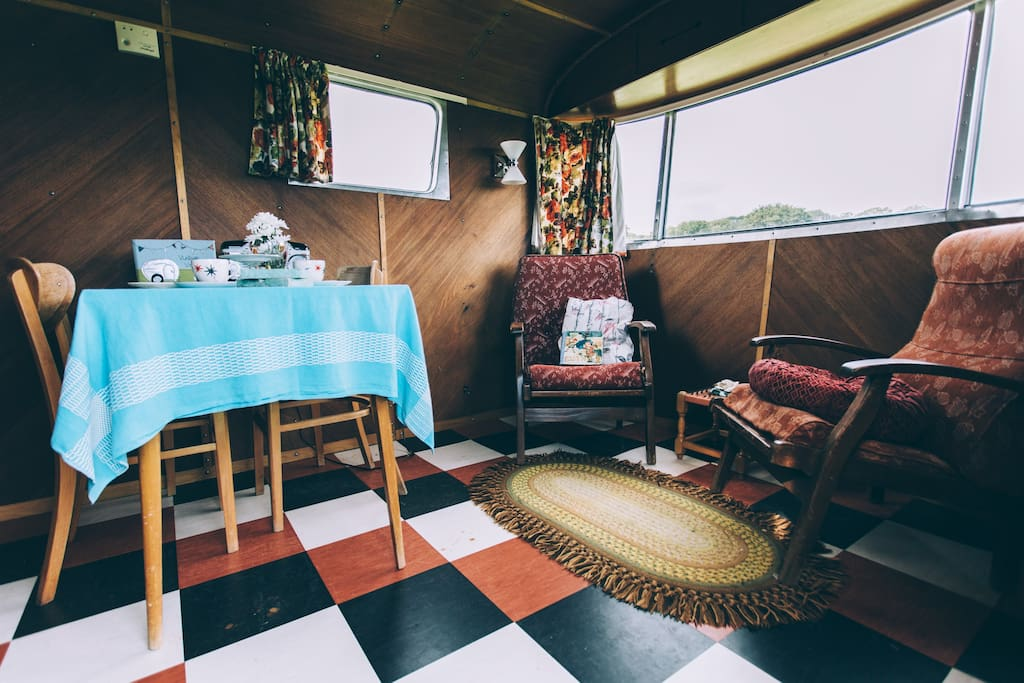 The living area with table and chairs and some cosy armchairs.