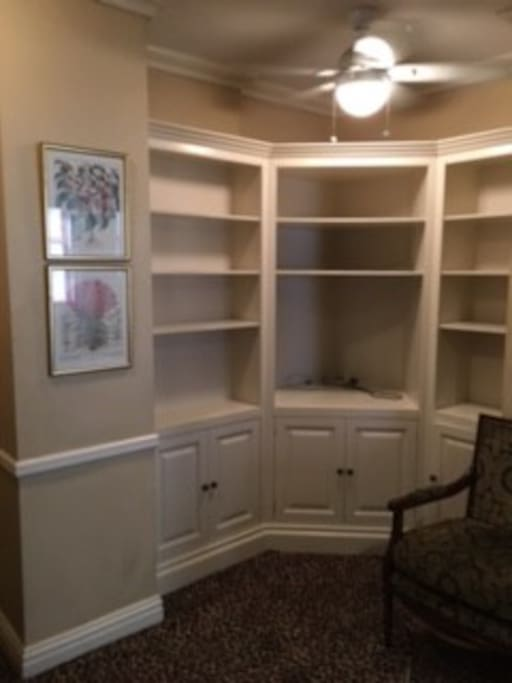 Freshly painted shelves and cabinets hold convection toaster oven, microwave, Keurig coffee maker and mini-fridge and lots of storage space