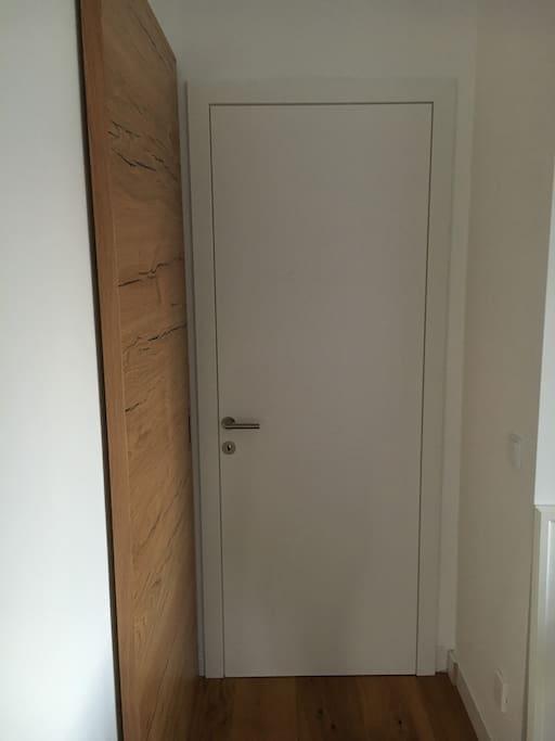 Das ist die Eingangstür in dein Zimmer, gleich links davon ist das Bad