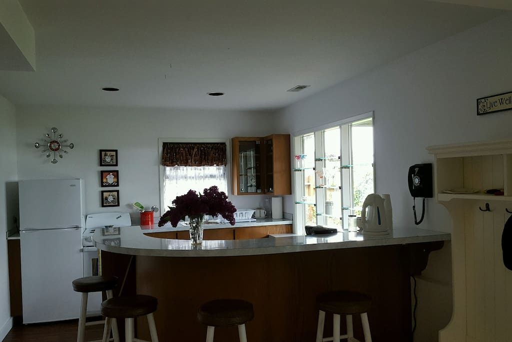 Bright kitchen space with view and breakfast bar with seating for 4.