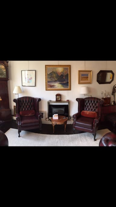 Comfortable living room with leather Club armchairs and Chesterfield 3-seater sofa.