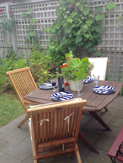French doors lead to a lovely courtyard  private garden with outdoor eating area and BBQ
