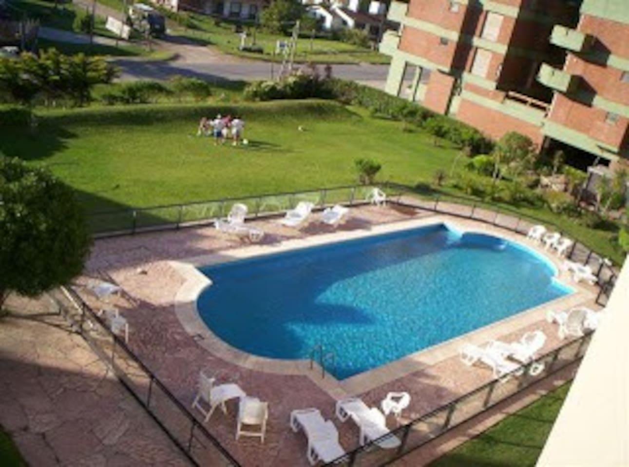 Gran piscina, solarium, repoceras, mesas y sillas con sombrillas en un gran parque.
