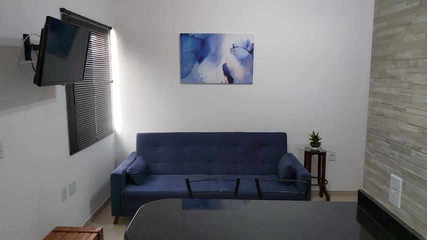 Sala com TV e sofá cama confortável.