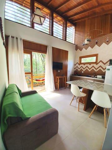 """Sala e cozinha integradas! Ambiente amplo com acabamento de alto padrão.   Com uma linda vista para bromélias em meio as árvores!   Smart TV de 32"""", sofá cama, tudo novo e super confortável!"""