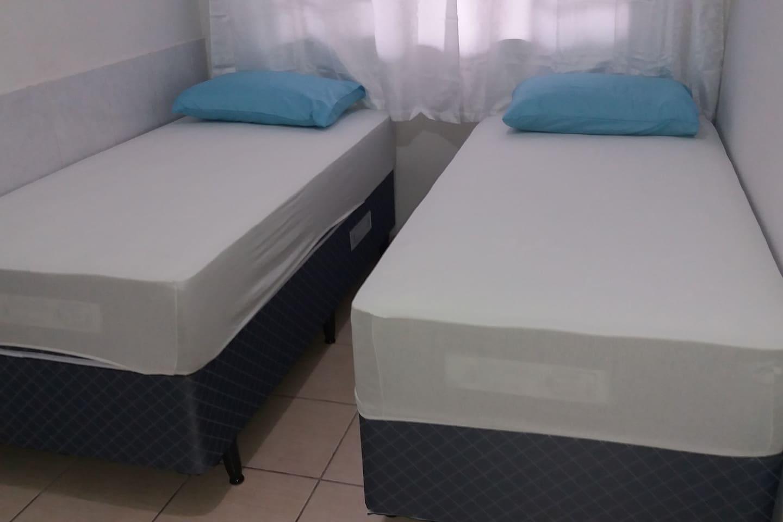 Quarto com duas camas de solteiros,armario e um ventilador.
