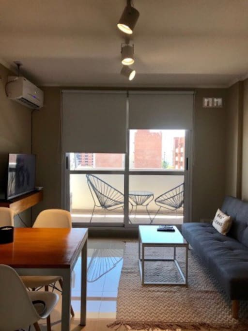 Living comedor con salida al balcon , sofa cama , smart 40 pulgadas , 4 sillas con mesa , mesa ratona sobre alfombra todo decorado para que te sientas como en tu casa .