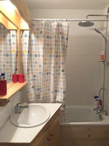 """Salle de bains avec baignoire et colonne de douche """"Jet de pluie"""". Lavabo, sèche serviette électrique. Vous trouverez le sèche cheveux sous le lavabo."""