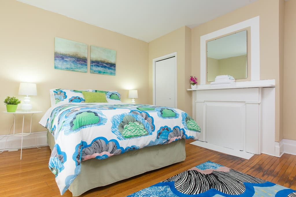 First bedroom on main floor, featuring cheerful decor and a brand new high-end queen bed for cozy sleeps.